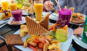 Brunch with susages, tomatoes, fruit, toast, coffee and orange juice